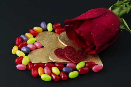 A single, red rose is placed on a black background with wo gold hears, two red hearts, and colorful jelly beans;  photo