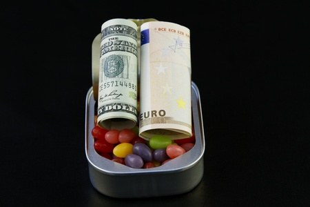 sardine can: American dollar and EU Euro set on colorful jellybeans in open sardine can to signify strategic diversifications role in sweetening savings Stock Photo