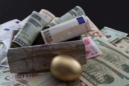 Rolled Euro and Dollar currency with gold nest egg on global currencies to depict worldwide emphasis on funding retirements and social network benefits Stock Photo