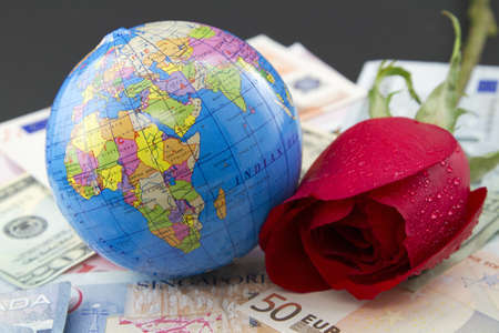 global retirement: Globe, red rose, and multiple national currencies reflect pleasure and success in worldwide travel, learning, and business