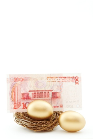 Chinas currency placed behind a gold nest egg in a twig nest with a 2nd gold nest egg near portrays Chinas growing economic influence on investments