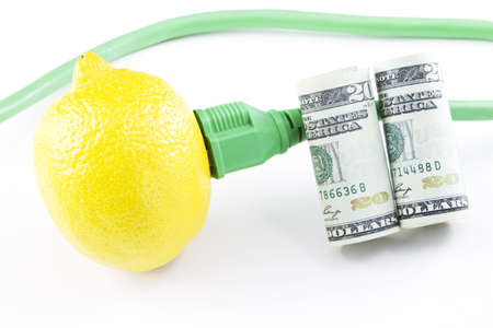 initiatives: Electric power outlet plugged into a fresh lemon with cord visible and American currency on the right depict modern investment and venture capital development into green energy and clean power initiatives; environmental juice;