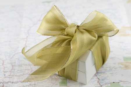 White box with gold ribbon on indistinct map; happy travels;