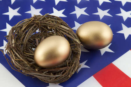 Two, gold eggs, one in twig nest and one directly on American flag, depict the financial building of personal as well as national prosperity