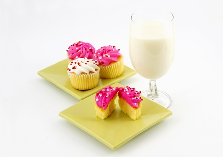 Simple celebration is established with a glass of milk, a halved vanilla cupcake with pink icing, and on a separate light green plate additional vanilla cupcakes, one with white icing, all on white background. Stock Photo