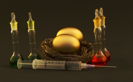 underlying: Two, gold eggs in twig nest with green and red fluid-filled research beakers next to a syringe depict the successful research and development underlying business profits