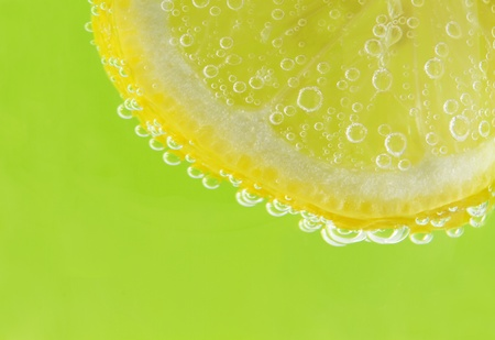 seltzer: A slice of lemon is accented with seltzer bubbles against a fresh, spring green background