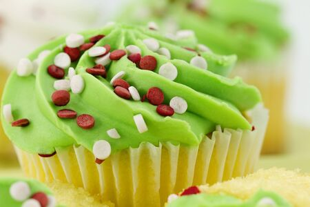 Close up of vanilla cupcake with green frosting and red and white sprinkles with defocused background is a fresh and sweet temptation
