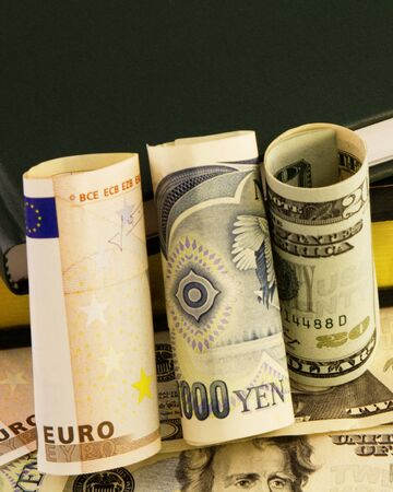 depict: Rolled  bills of euro, yen, and dollars are placed against ledgers and currency to depict global financial issues. Stock Photo