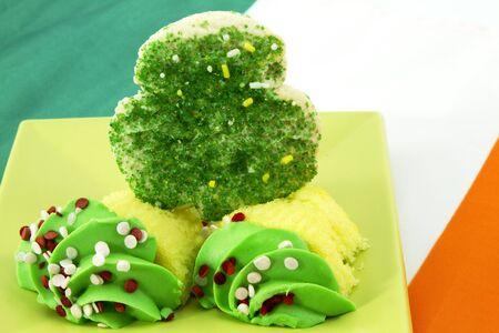 Shamrock sugar cookie with sliced cupcake with green frosting are placed on an Irish flag to highlight a St. Patricks Day dessert or snack. photo