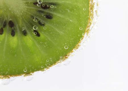 Kiwi fruit slice submerged in bubbling seltzer water creates a sense of energetic refreshment.