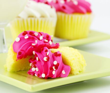 Cupcakes are placed, sliced one in foreground and whole ones in back, on light green plates with a glass of milk.  Pink icing, vanilla cupcakes  in back and milk are unfocused in contrast to front dessert.   Stock Photo - 8945808