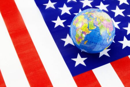 A world globe is placed on the traditional red, white, and blue American flag reflecting Americas integral global involvement Imagens