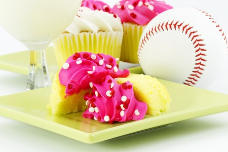 Vanilla cupcakes with pink icing, white milk, and a baseball suggest a festive, after game celebration Stock Photo - 9063937