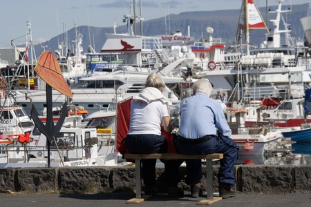 Reykjavik, Iceland - July 13, 2009:  Mature man and woman sit on bench at Reykjaviks Old Harbor area.  The old harbor was originally built 1913-17.  It is popular spot in Icelands capital city for locals and tourists to stroll.