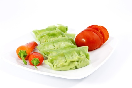 Vegetable gyoza, fresh red peppers, and sliced tomatoes on a white plate make for a vegetarian delight; gyoza is a Japanese dumpling. Stock Photo