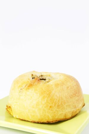 Potato Knish, a baked dumpling filled with potato, sits on green plate; copy space above; potato knish is a Yiddish snack food, a Jewish dinner staple, or simply a delicious, vegetarian dish.  Stock Photo