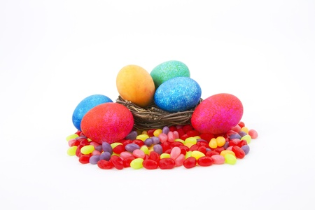 Mottle colored Easter eggs in a natural twig nest sit on colorful jelly beans photo