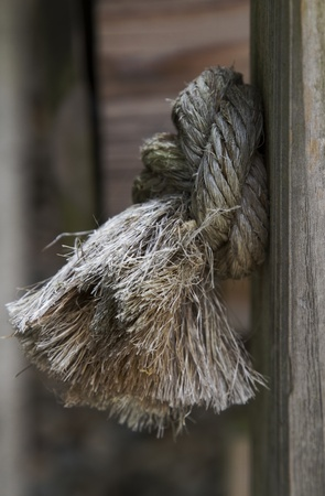 Firmly knotted rope is pressed against its post hole in a knotty problem metaphor