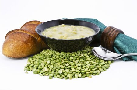 napkin ring: Split pea soup in black bowl with fresh loaf of bread, green napkin and brown wood napkin ring on dried  peas ingredient against white background