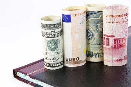 Close up of four major global currencies, US dollar, Euro, yen, and yuan, placed on a leather ledger book Stock Photo