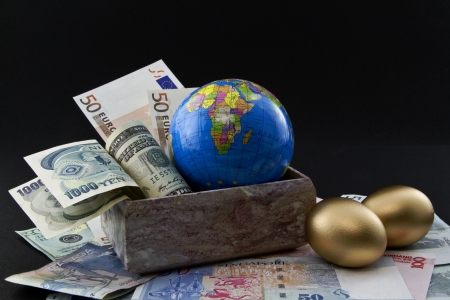 Multiple world currencies including yen, dollar, and euro in a marble box next to two, gold nest eggs