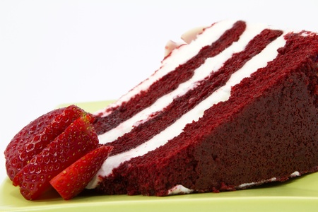 A slice of red velvet cake with white frosting is garnished with strawberries and placed on a square, green plate; close up; white background; photo