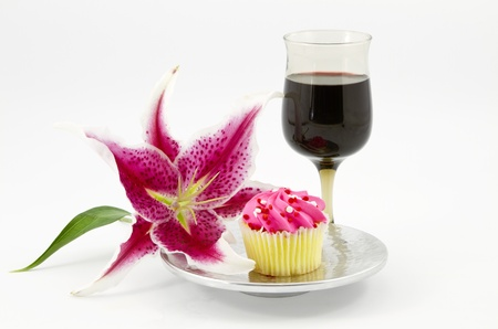 Elegant lily is placed next to cupcake on silver plate accompanied by red wine in stem glass; white background; horizontal;