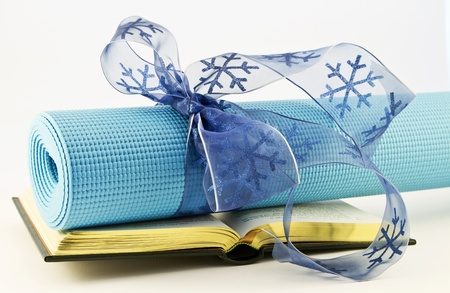 Serene blue yoga mat wrapped with blue ribbon placed with open book; fitness, study, and yoga are gifts of healthy lifestyle.   Stock Photo