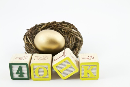 Gold nest egg sits behind alphabet blocks spelling 401K in a concept image of saving for retirement and future goals
