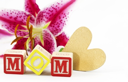 Gold heart and alphabet block letters spelling MOM are placed in front of a  single, lily blossom against a white background