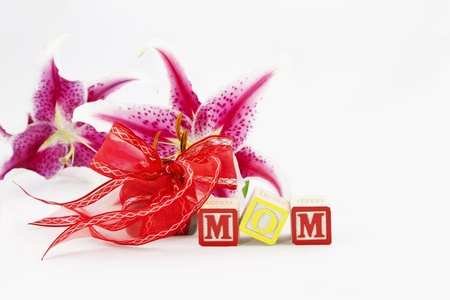 Alphabet blocks spelling out MOM are in front of a red ribbon wrapped gift and two, single lily blooms, all placed on a white background.