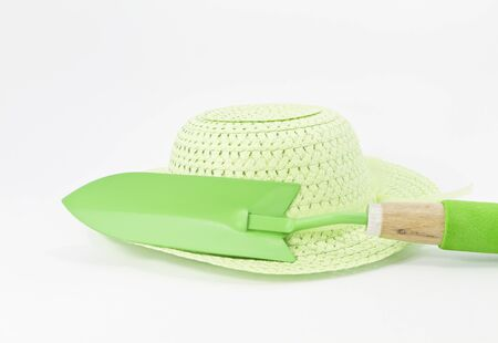 cushioned: Light green, straw hat with green trowel with wood and green cushioned handle on a white background Stock Photo