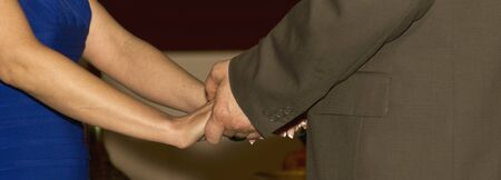 Long crop of male and female adults with hands held.  Male is in brown suit and female wears a blue dress.   photo