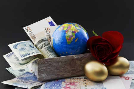 financial diversification: Diverse currencies including yen, euro, US, Singapore, Canada, and China are in and around a marble box containing a globe with a rose and gold nest eggs in front