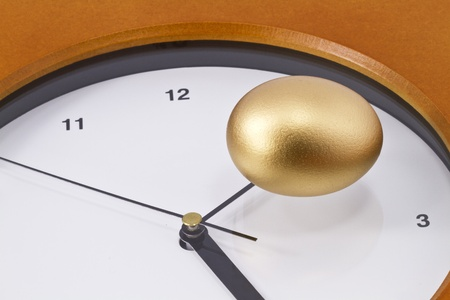 Gold nest eggs sits on ticking clock Stock Photo