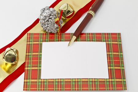 Plaid framed note with open space placed with pen and holiday items of ribbon, gold bells, and silver pine cone;
