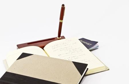 Open, notated journal, desk pen, passport, and 2nd journal
