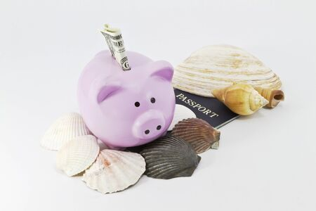 Pig-shaped bank with sea shells and passport reflect savings for summer travel Stock Photo