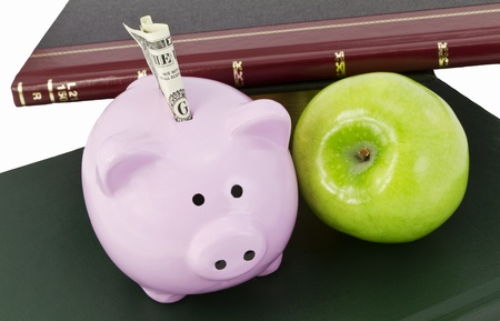 Piggy bank with currency at top shown with books and green apple reflect education dollars, savings for school expenses.
