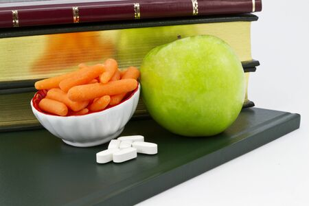 Healthy carrots and a green apple placed with calcium supplement pills with books behind