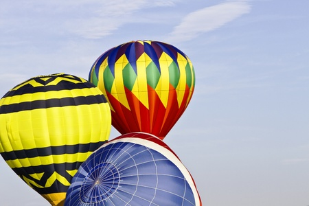 Three hot air balloons inflate in preparation for a dawn mass ascension; copy space to right; Location is New Jersey Festival of Ballooning; Stock Photo