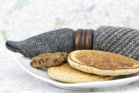 Pancakes with sausages and black and gray woven napkin on white plate with map background; selective focus on food; emphasis on importance of good breakfast before and during business or leisure travel; Stock Photo