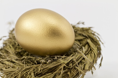 Closeup of gold nest egg set in sparkling gold nest; selective focus on nest egg;