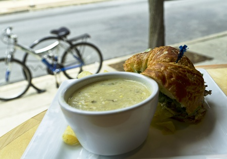 Soup and sandwich stop with bicycles parked outside and visible through restaurant window; cup of vegetable chowder with croissant bread, vegetable sandwich, edge of potato chip showing.