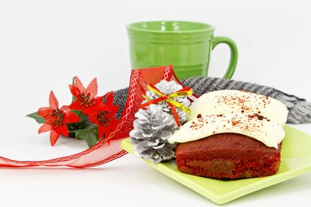 Christmas details placed with mini-loaves of red velvet cake, woven napkin, and green coffee mug.