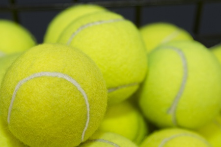 Practice, tennis balls are piled high, waiting for lessons or game preparation.  Stock Photo