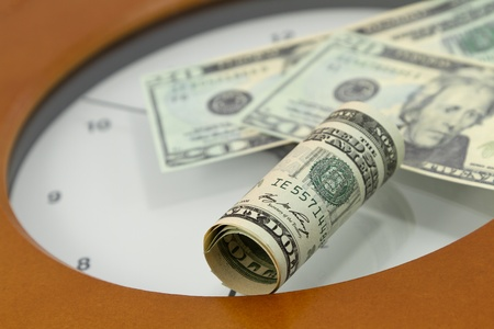 American currency placed on face of clock is indicative of times relationship to money in investments, unique financial times, and financial urgency at specific points in life.