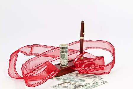 christmas bonus: Cash placed with whirl of red ribbon and rosewood pen captures holiday spirit of a Christmas or year end cash bonus