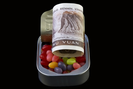 Chinas currency, yuan, showed in opened can filled with candy and money, reflects business investment and growth in Chinas economy. photo
